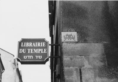 שלט ברובע יהודי במריי, פריס, לצד אחד מהספייס אינוויידרס הרבים בעיר
